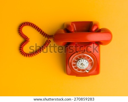 upper view of red phone with heart shape made out of its cable, on yellow background - stock photo