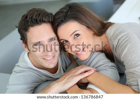 Upper view of sweet couple sitting in sofa - stock photo