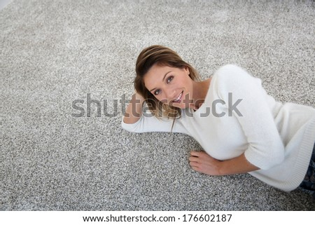 Upper view of woman relaxing on carpet at home - stock photo