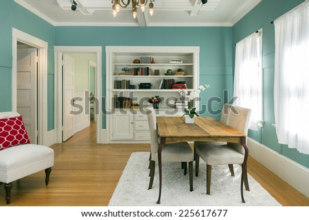 Upscale dining room in villa in turquoise / light blue with white trimmings, wooden floor, book shelf and table with chandelier. - stock photo
