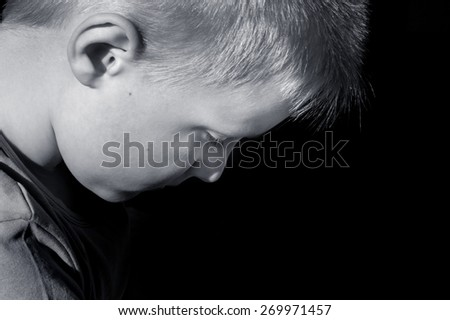 Upset abused frightened little child (boy),  close up horizontal dark portrait with copy space - stock photo