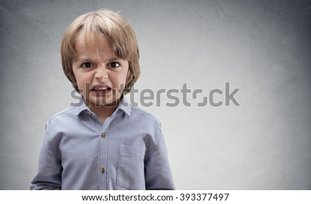 Upset and angry boy concept for anger, frustration and mischief with copy space - stock photo