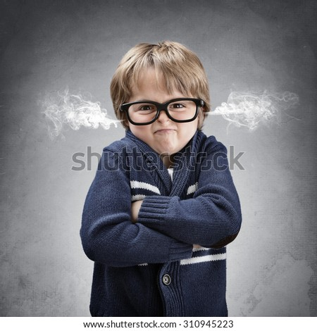 Upset and angry boy with steam coming from his ears and arms folded concept for anger, frustration and mischief - stock photo