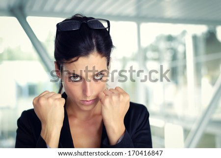 Upset and challenging businesswoman ready to fight. Female executive with furious eyes and raised fists. - stock photo