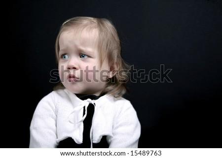 Upset baby girl on black background - stock photo