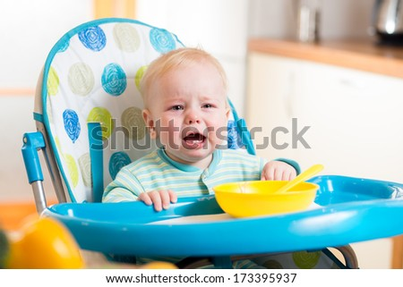 upset baby sitting in highchair for feeding - stock photo