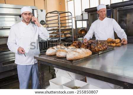 Upset baker making phone calls in the kitchen of the bakery - stock photo