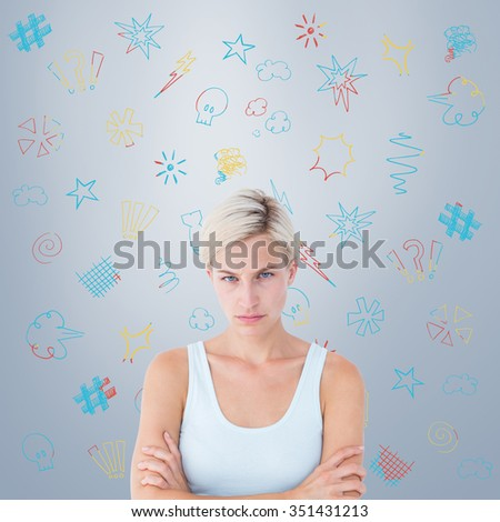 Upset blonde looking at camera with arms crossed against grey vignette - stock photo