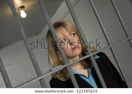 Upset businesswoman standing behind bars in jail - stock photo