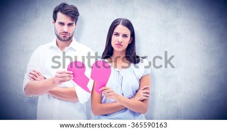 Upset couple holding two halves of broken heart against white background - stock photo