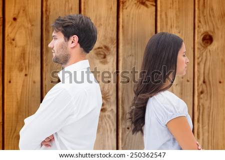 Upset couple not talking to each other after fight against wooden background - stock photo