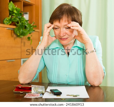 Upset female pensioner looking at bills and counting money   in home - stock photo