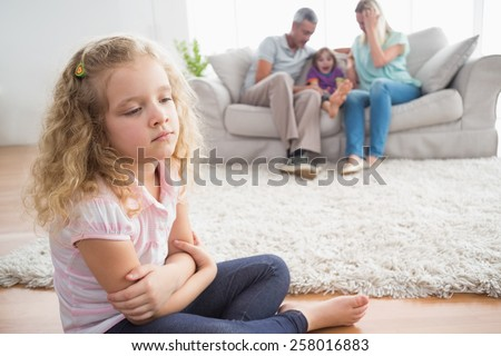 Upset girl sitting on floor while parents enjoying with brother on sofa at home - stock photo