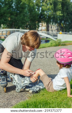 Upset girl with a knee wounded, her skating trainer trying to calm her - stock photo