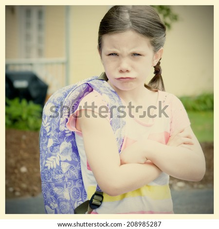 Upset little girl with backpack and instagram style filter - stock photo