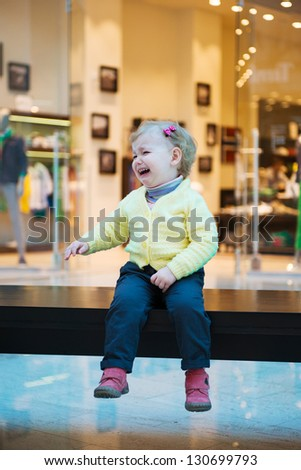 Upset little lost girl sitting on bench in mall - stock photo