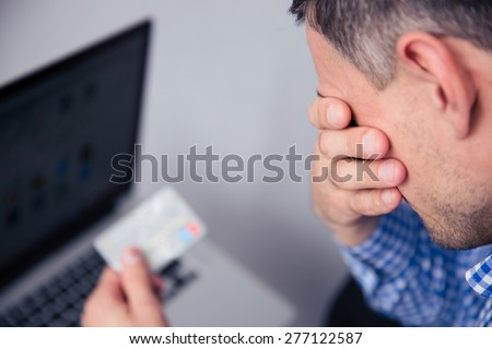 Upset man holding credit card with laptop on background - stock photo