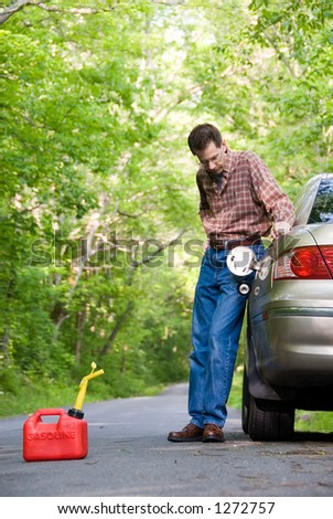Upset man on a country road, staring at a gas can sitting  on the road next to his car.  Focus is on the gas can. - stock photo