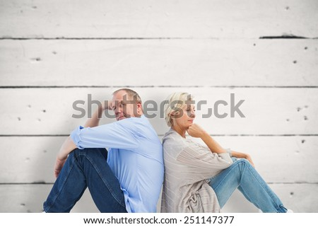 Upset mature couple not talking against white wood - stock photo