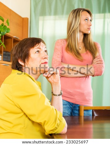 Upset mature mother against adult daughter after conflict   - stock photo
