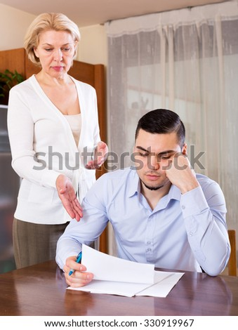 Upset mature woman and young boyfriend with invoices for payment. Focus on the man - stock photo