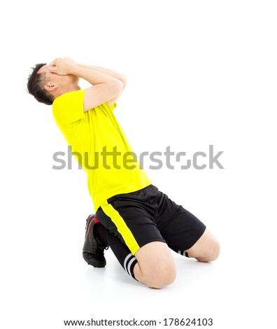 Upset  or excited soccer player kneeling down - stock photo