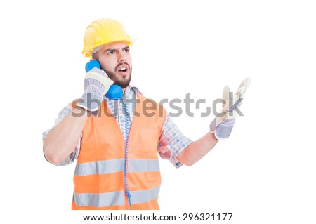 Upset or mad builder arguing on the phone wearing yellow helmet and orange vest - stock photo