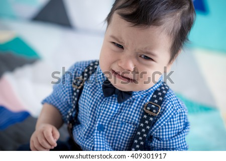 Upset, sad cute 11 month old mixed race Asian Caucasian boy dressed in braces and bow tie on a colourful geometrically shaped bed cover - stock photo