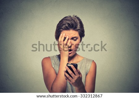 Upset stressed looking woman holding cellphone disgusted shocked with message she received isolated grey background. Human face expression emotion feeling reaction life perception body language - stock photo