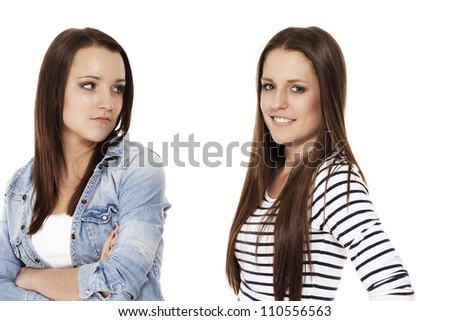 upset teenager looking to her happy friend on white background - stock photo