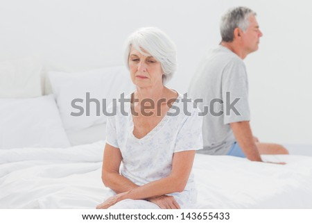 Upset woman arguing with husband on bed - stock photo