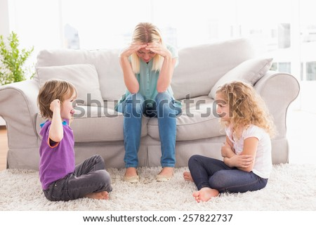 Upset woman sitting on sofa while brother teasing sister at home - stock photo