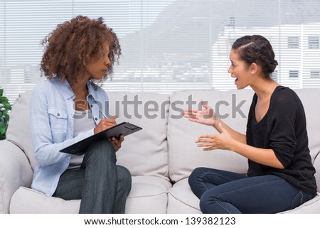 Upset woman speaking to her therapist while she is taking notes - stock photo