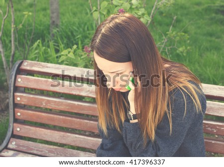 Upset woman talking on the mobile phone sitting on a park bench - stock photo
