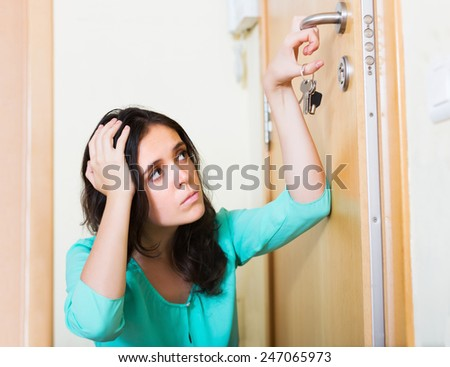 Upset woman trying to lock front door with key - stock photo
