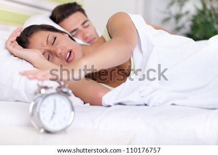 Upset woman turn off alarm clock, Wake up early morning. - stock photo