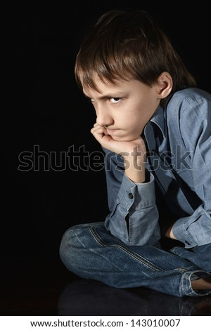 upset young boy on a black background - stock photo