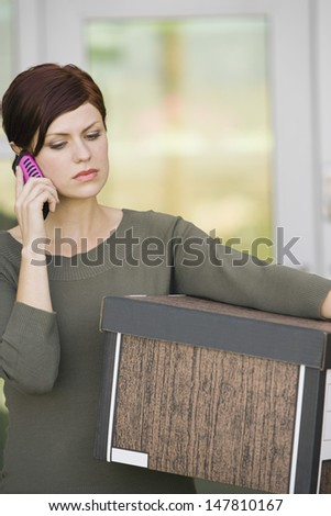 Upset young businesswoman using mobile phone while carrying moving box - stock photo