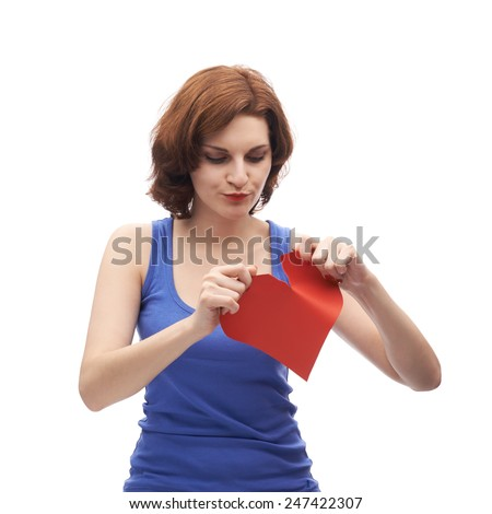 Upset young caucasian woman in her twenties tearing red heart in two halves, composition isolated over the white background - stock photo