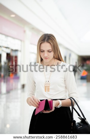 Upset young woman in shopping mall checking her purse with troubled look. Out of money, broke - stock photo