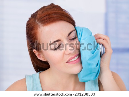 Upset young woman touching cheek with hot water bag at home - stock photo