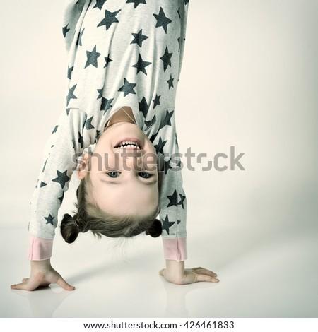 Upside down funny portrait of little happy sleepless girl in pajamas. - stock photo