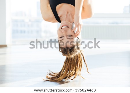 Upside down view of happy pretty young woman with dreadlocks talking on mobile phone - stock photo
