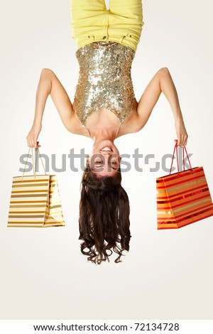 Upside down view of young girl with paperbags on white background - stock photo