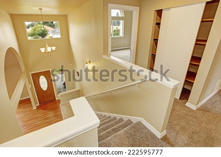 Upstairs hallway with staircase with panoramic view on entrance hallway with archway - stock photo
