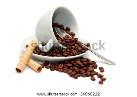 Upturned cup with coffee beans and candy - stock photo