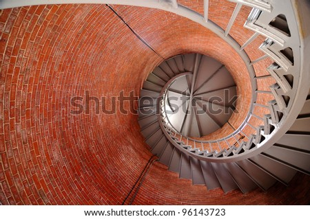 Upward spiraling stairway inside a red brick lighthouse - stock photo