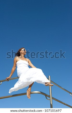 Upward view of attractive mature woman in white summer dress sitting happy and relaxed on metal railing bare feet, isolated with blue sky as background and copy space. - stock photo