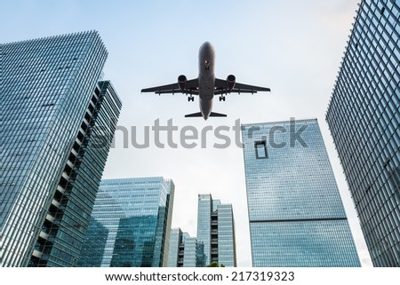 upward view of the airplane with modern office buildings  - stock photo