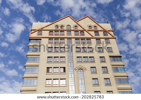 Upward view on modern luxury apartment against cloudy blue sky - stock photo